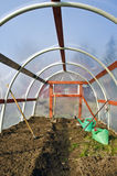 Early spring  greenhouse inside construction with gardener tools and  soil Royalty Free Stock Photo