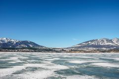 Early spring landscape of frozen Columbia Lake Regional District of East Kootenay Canada. Nature snow cold winter blue ice mountain white beautiful travel water stock photo
