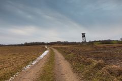 Early spring landscape with raised hide. Winter or early spring landscape of field with raised hide under cloudy sky. Sad landscape Royalty Free Stock Photography