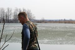 The man stares into the distance while standing on the shore of the lake. stock image