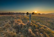 Early spring meadow with barbed wire fence at sunset Stock Photography