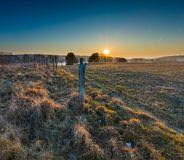 Early spring meadow with barbed wire fence at sunset Stock Photos