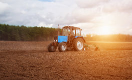 In the early,spring morning,because of the wood the bright sun ascends.The tractor goes and pulls a plow,plowing a field before la Royalty Free Stock Image