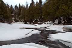 Early Spring in Northern Minnesota and Cascade River showing thru ice and snow. This is Spring, days become warmer and ice getting thinner. Cascade River in stock photo