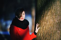 Early spring portrait of cute attractive serious young girl. With dark hair heat scarf and red jacket looking to camera and standing on wild forest natural Stock Photos