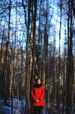 Early spring portrait of cute attractive serious young girl with dark hair heat scarf and red jacket looking to camera and standin Stock Image