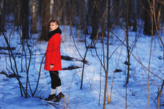 Early spring portrait of cute attractive serious young girl with dark hair heat scarf and red jacket looking to camera and standin Stock Photos