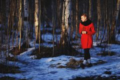 Early spring portrait of cute attractive serious young girl. With dark hair heat scarf and red jacket looking to sun and walking through the woods with a sprig Royalty Free Stock Images