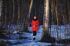 Early spring portrait of cute attractive serious young girl with dark hair heat scarf and red jacket looking to sun and walking th. Rough the woods with a sprig Royalty Free Stock Image