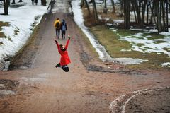 Early spring portrait of cute attractive young girl with dark hair heat scarf and red jacket looking to camera and jumping for joy Royalty Free Stock Photography