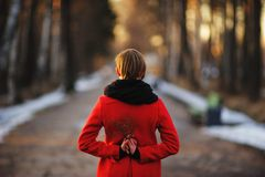 Early spring portrait of cute attractive young girl with dark hair heat scarf and red jacket standing in the middle of the road in Royalty Free Stock Images