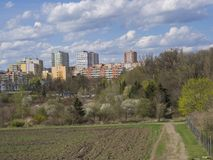 Early spring Prague landscape with high-rise apartment building, brown field, green grass, trees with fresh lush leaves and blue royalty free stock image