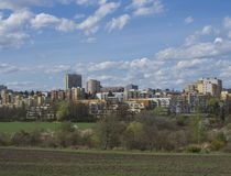Early spring Prague landscape with high-rise apartment building, brown field, green grass, trees with fresh lush leaves and blue stock photography