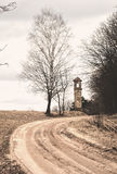 Early spring road, birch and old belfry Stock Photo