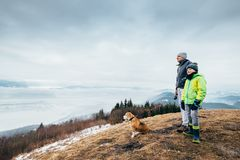 Early spring time - father with son walk with dog on mountain hi. Lls Stock Photos