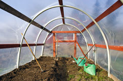 Early spring time greenhouse inside construction with gardener tools Royalty Free Stock Photos