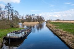 Early spring view on Giethoorn, Netherlands, a traditional Dutch village with canals. A typical low boat along the lawn in a royalty free stock images