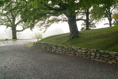 Early Stacked Stone Wall Along  A Road. Early stacked stone wall along a hillside road on a foggy morning Royalty Free Stock Images