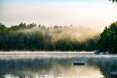 Mist clearing of lake. Early summer morning, docks with the ladders, & boats, as the mist rises off the reflective lake Royalty Free Stock Image