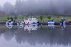 Early summer morning by the lake with motor boats Stock Images