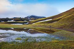 Early summer morning in the National Park Landmannalaugar, Iceland. Snow lies in the hollows of colorful rhyolite mountains. Green stock photos