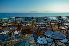 Early Summer Morning on the Wooden Terrace with View of the Calm Sea and Distant Mountains stock photo