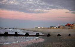 Early sunrise on the beach. Beach on the coast of New Jersey. The first rays of sunrise close the sky and the water in pink color royalty free stock images