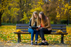 Early warm fall. Two charming girls sit on a bench in the autumn park. Royalty Free Stock Photo