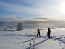 Early winter morning. Two people enjoy the early morning at hills in winter Stock Photo