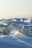 Early winter morning at Lake Baikal. rising sun colors the snow in shades of ultraviolet. Crystal clear transparent ice pieces Royalty Free Stock Photos