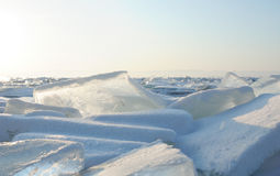 Early winter morning at Lake Baikal. rising sun colors the snow in shades of ultraviolet. Crystal clear transparent ice pieces Stock Photos