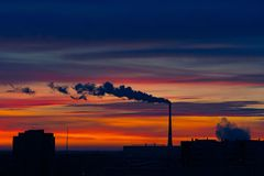 Early winter morning over the city. Red-blue bright sky. The sun has not yet risen. The city begins to wake up. Only the pipe already in full smokes Royalty Free Stock Images