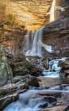 Early Winter Than at Kaaterskill Falls. A rainbow shines at Kaaterskill Falls during a late February thaw in the Catskill Mountains of Greene Country, New York Stock Image