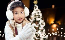 Earmuffs счастливой девушки нося над светами рождества Стоковые Фото