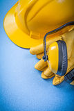 Earmuffs protective gloves building helmet on blue background  Royalty Free Stock Images