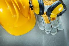 Earmuffs protective gloves building helmet on concrete backgroun Stock Photography