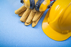 Earmuffs safety gloves building helmet on blue background constr Stock Photos