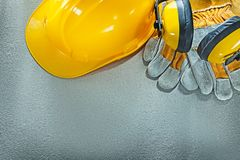 Earmuffs safety gloves hard hat on concrete background Royalty Free Stock Photos