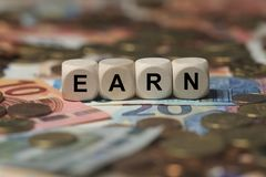 Earn - cube with letters, money sector terms - sign with wooden cubes Stock Images