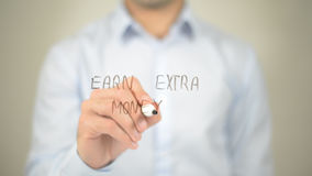 Earn Extra Money , man writing on transparent screen Royalty Free Stock Photography