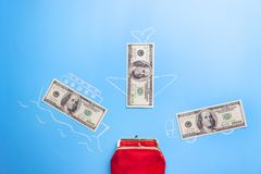 Earn money concept. Dollars go into red wallet royalty free stock photo