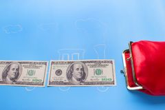 Earn money concept. Dollars go into red wallet royalty free stock images