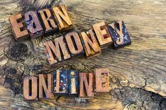 Earn money online letterpress. Small business concept earn money online computer home business earning letterpress sign message wood block type letters royalty free stock image