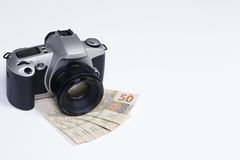 Earn money with photography. Camera photographic upon Brazilian real notes on white surface Royalty Free Stock Photography