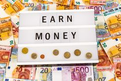Earn Money. Text  Earn Money written on lightbox surrounded with Euro Banknotes Stock Images