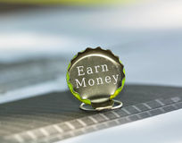 Earn money. Text written on a metal bottle cap over a blue background Stock Images