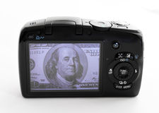 Earn with stock photography. Camera with 100 dollars shot on a display Royalty Free Stock Images