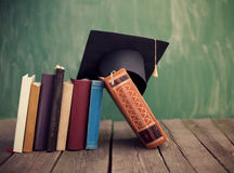 Earn your graduation cap. Graduation cap on standing books Stock Image