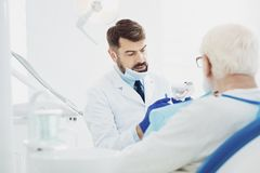 Earnest male dentists explaining details stock images
