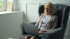 Attentive woman working at home. Earning money. Waist up of attentive middle aged woman using a laptop while expressing concern stock video